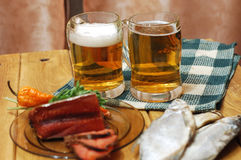 Beer and fish on table. Mugs with beer and dried fishes Stock Photography