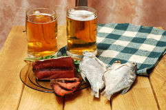 Beer and fish on table. Mugs with beer and dried fishes Stock Image