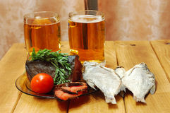 Beer and fish on table. Mugs with beer and dried fishes stock photos