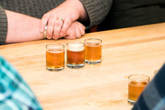 Beer flight tasting at a Brewery. A flight of three beers presented in front of a man at a brewery Royalty Free Stock Photography