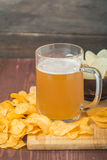 Beer with foam in glass mug and potato chips Stock Image