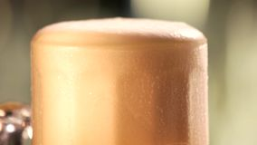 Beer foam motion. Slowly dripping beer foam out of glass, close up stock footage
