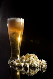 Beer with foam and popcorn Royalty Free Stock Image