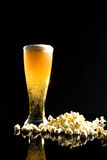 Beer with foam and popcorn Stock Image