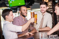 Beer and football in the bar. Three other men drinking beer and Royalty Free Stock Photography