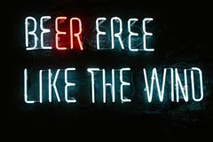 Beer free like the wind neon inscription on dark wall. In bar royalty free stock photo