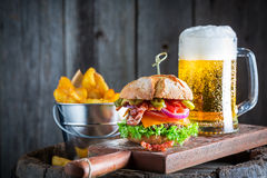 Beer and fresh hamburger made of beef, cheese and vegetables Royalty Free Stock Photography