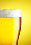 Beer with froth. Glass of beer with froth close-up over yellow background royalty free stock images