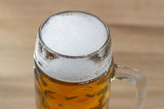 Beer with a frothy head in a glass beer mug. Close up high angle view of beer with a good frothy head in a glass beer mug or tankard standing on a wooden bar Stock Image