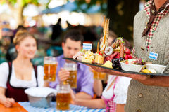 In Beer garden - beer and snacks. In Beer garden in Bavaria, Germany - beer and snacks are served, focus on meal stock photography