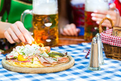 Beer garden - friends with beer and snacks in bavaria. In Beer garden - friends in Tracht, Dirndl and Lederhosen with snacks drinking a fresh beer in Bavaria royalty free stock image