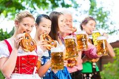 Beer garden - friends drinking in Bavaria Pub. In Beer garden - friends, men and women in Tracht, Dirndl and Lederhosen drinking a fresh beer in Bavaria, Germany stock photos