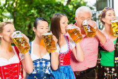 Beer garden - friends drinking in Bavaria Pub. In Beer garden - friends, men and women in Tracht, Dirndl and Lederhosen drinking a fresh beer in Bavaria, Germany royalty free stock photo