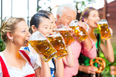 Beer garden - friends drinking in Bavaria Pub. In Beer garden - friends, men and women in Tracht, Dirndl and Lederhosen drinking a fresh beer in Bavaria, Germany royalty free stock images