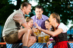 In Beer garden - friends drinking beer Stock Images