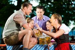 In Beer garden - friends drinking beer. In Beer garden - friends in Lederhosen drinking a fresh beer stock images