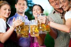 In Beer garden - friends drinking beer. In Beer garden - friends in Tracht, Dindl and Lederhosen drinking a fresh beer in Bavaria, Germany stock photography