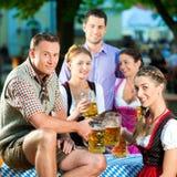 In Beer garden - friends drinking beer. In Beer garden - friends in Tracht, Dindl and Lederhosen drinking a fresh beer in Bavaria, Germany stock images