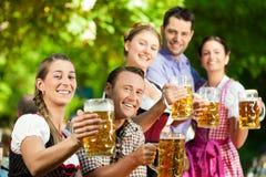 In Beer garden - friends drinking beer. In Beer garden - friends in Tracht, Dirndl and Lederhosen drinking a fresh beer in Bavaria, Germany royalty free stock photo