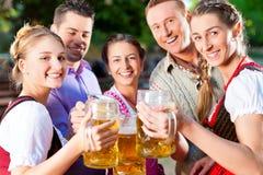 In Beer garden - friends drinking beer. In Beer garden - friends in Lederhosen drinking a fresh beer in Bavaria, Germany royalty free stock images