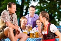 In Beer garden - friends drinking beer. In Beer garden - friends in Lederhosen drinking a fresh beer in Bavaria, Germany stock photography