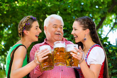 In Beer garden - friends drinking beer in bavaria Stock Image