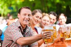 In Beer garden - friends drinking beer. In Beer garden - friends in Lederhosen drinking a fresh beer in Bavaria, Germany stock image