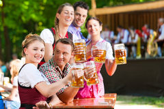 In Beer garden - friends in front of band. In Beer garden in Bavaria, Germany - friends in Tracht, Dirndl and Lederhosen and Dirndl standing in front of band royalty free stock photos