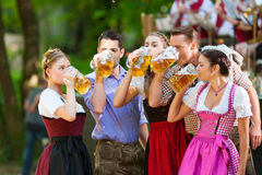 In Beer garden - friends in front of band. In Beer garden in Bavaria, Germany - friends in Tracht, Dirndl and Lederhosen and Dirndl standing in front of band stock images