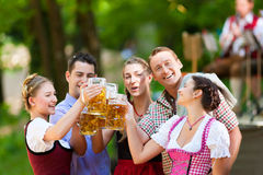 In Beer garden - friends in front of band. In Beer garden in Bavaria, Germany - friends in Tracht, Dirndl and Lederhosen and Dirndl standing in front of band stock photography