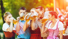 In Beer garden - friends in front of band. In Beer garden in Bavaria, Germany - friends in Tracht, Dirndl and Lederhosen and Dirndl standing in front of band royalty free stock photography