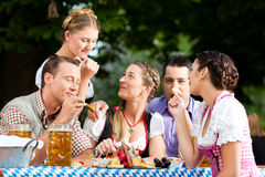 In Beer garden - friends on a table with beer. And snacks royalty free stock photography
