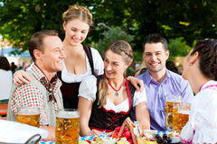 In Beer garden - friends on a table with beer. In Beer garden - friends Tracht, Dirndl and on a table with beer and snacks in Bavaria, Germany royalty free stock image