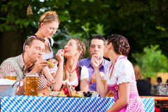 In Beer garden - friends on a table with beer. In Beer garden - friends Tracht, Dirndl and on a table with beer and snacks in Bavaria, Germany stock photography