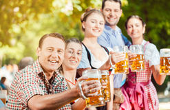 In Beer garden - friends drinking beer in Bavaria on Oktoberfest. In Beer garden - friends in Tracht, Dirndl and Lederhosen drinking a fresh beer in Bavaria stock photography