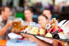 Beer garden restaurant - beer and snacks. Beer garden restaurant in Bavaria, Germany - beer and snacks are served, focus on meal stock image