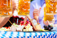 Beer garden restaurant - beer and snacks. Beer garden restaurant in Bavaria, Germany - beer and snacks are served, focus on meal royalty free stock images