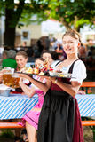 Beer garden restaurant - beer and snacks. Beer garden restaurant in Bavaria, Germany - beer and snacks are served, the waitress also wears traditional costume royalty free stock photo