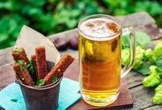 Beer with garlic rye croutons outdoors. Beer with garlic rye croutons on table in garden outdoors royalty free stock photography