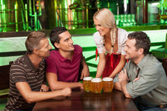 Beer for gentlemen. Beautiful young waitress serving beer while Royalty Free Stock Image