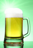 Beer with glare. Mug of beer with glare over green background Stock Photos