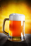 Beer in a glass. Over gold background royalty free stock image