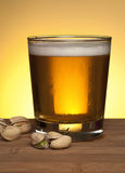 Beer in glass. Cold delicious frothy beer in glass with nuts on wood table against golden yellow background Royalty Free Stock Photography