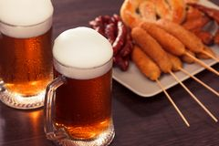 Beer glass alcohol drink with food sausage,  grilled pretzel stock photography
