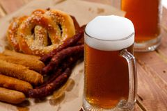 Beer glass alcohol drink with food sausage,  pretzel stock image