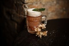 Beer glass with alcoholic drink decorated with moss and dried flowers stock photography
