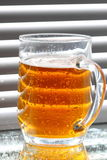 Beer glass blinds sunlight E Royalty Free Stock Photos