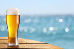 Beer glass on a blurred background of the sea. Stock Photos