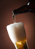 Beer glass and bottle on a brown Royalty Free Stock Photo