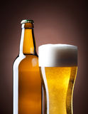 Beer glass and bottle on a brown Stock Photography